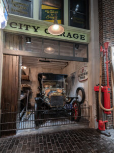 A black 1900's vehicle sits in a garage that is gated off from the wooden cobblestones streets.