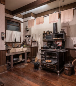 A 1890s kitchen with a wooden sink and iron stove. Area is full of cooking tools such as a waffle iron, kettle, and plates.
