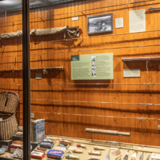 Display case with wood paneling that contains recreational fishing equipment such as poles, nets, and hooks.