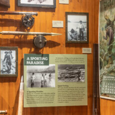 "A display case with wood paneling, which contains ends of two fishing poles with images and signs about ""A Sporting Paradise""."