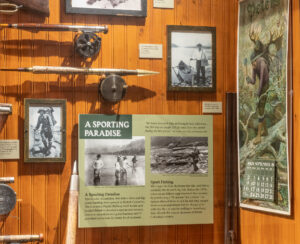 A display case with wood paneling, which contains ends of two fishing poles with images and signs about