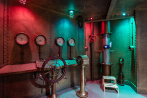 Medal walls of a replica submarine with a steering wheel, pressure dials, and periscope.
