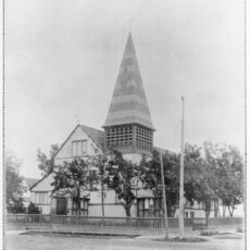 Black-and-white photo of a church, surrounded by a fence and trees.