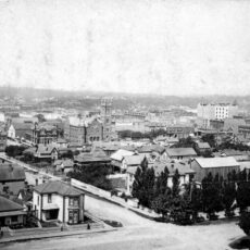 Black-and-white aerial image of Victoria along the harbour with dozens of houses and a large church.