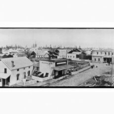 Black-and-white panoramic of wood buildings and muddy ground.