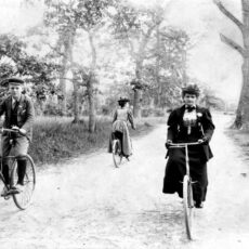 Black-and-white image of three people on bikes surrounded by trees.