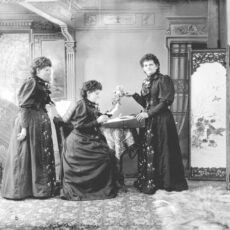 Black-and-white image that shows Hannah Maynard in three different positions in a fancy room (sitting down, looking over herself, and staring at the camera).