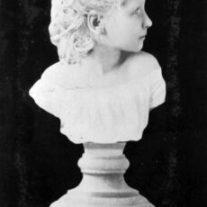 Black-and-white image sculpture of young girl's head and shoulders on top of a pedestal.