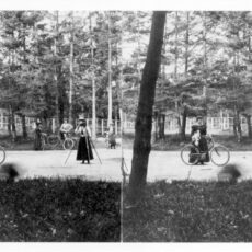 Black-and-white image of two almost identical images of trees and people standing beside bicycles.