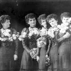 Black-and-white image of five Hannah Maynards. One flower chain is being held by two of them.