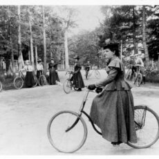 Black-and-white image of Hannah Maynard on a bicycle in a park with nine people holding their bikes in the background.