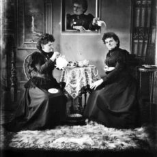 Black-and-white image. Two Hannah Maynards are sitting having tea while a third is coming alive in a painting to pour tea on one of the others.