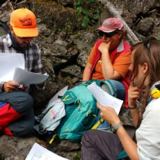 Three people sitting on rocks and examining papers and maps.