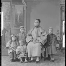 The black and white portrait consists of a group of unidentified individuals (1 adult seated, 4 youth standing), All of the sitters wear Asian garments and two individuals are holding fans.