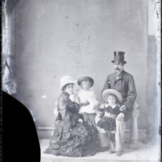 A black and white photo of a family a fancy dressed party. Included a man, women, and two children.