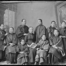 A black and white portrait of ten unidentified individuals (5 youth and adults seated and 5 youth and adults standing). Nine of the individuals wear Asian garments and one wears Western garments and the sitter holds a photograph in hand. It is a gelatin dry glass plate negative (8x10 inches).