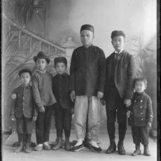 Black and white image of six boys. The majority of the sitters wear Western clothing, with one of the youth wearing both Asian garments and a cowboy hat and another adult sitter only Asian clothing.