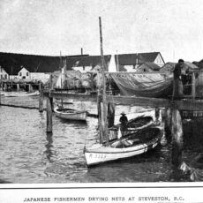 Several boats docked at the Steveston harbour. Two men stand near the boats to dry their fishing nets.