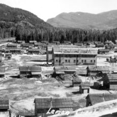 A large school building in the middle of a camp, surrounded by several houses and mountains