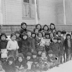Thirty-five students and teachers stand outside for a group photo. It is a snowy winter scene.