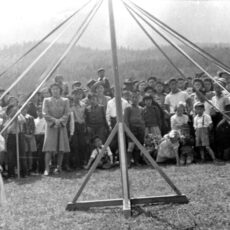Kindergarten students hold their ribbons around the maypole. Many adults and children gather to watch.