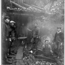 Alt text: Six Japanese Canadian miners stand in front of the mine with shovels and a wheelbarrow.