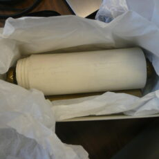 A large scroll wrapped in tissue paper is in a box.