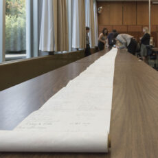 The scroll is rolled out on a long table. Five adults stand at the end of the table.
