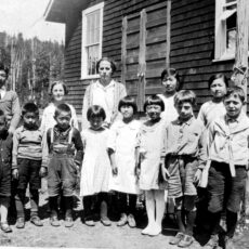 Eleven students and two teachers pose for a school photo outside the Ucluelet East School. The students are a mixed ethnic group.