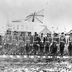 A group of Black soldiers in front of buildings, and under a flag.