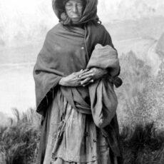 Woman standing, wearing a hood