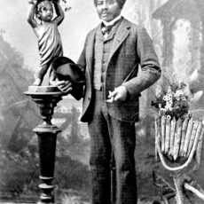 Man standing by statue, holding a hat.