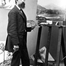 Man standing by easel with paintbrushes.
